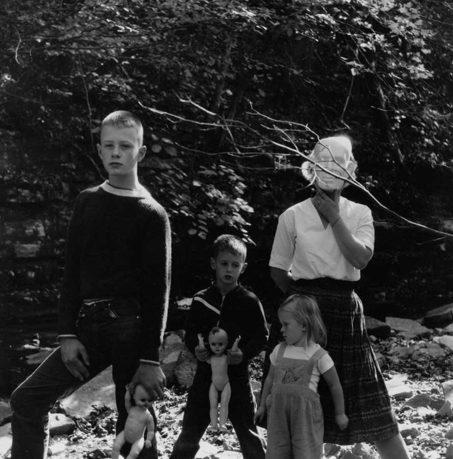 Black-and-white photograph of three children holding baby dolls and a woman holding a mask over her face