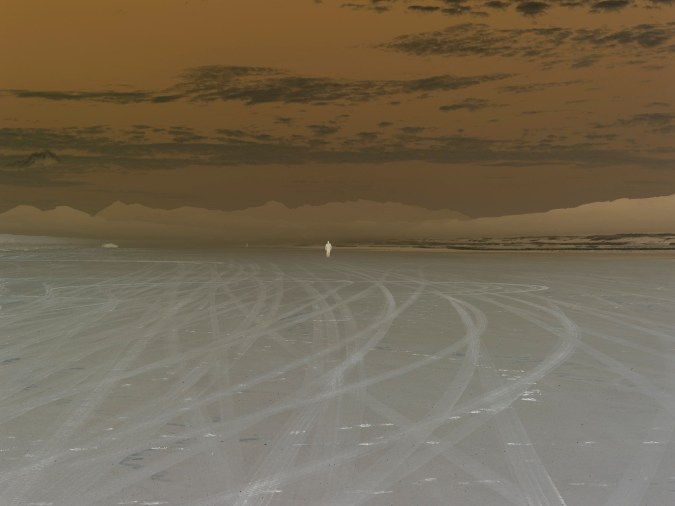Inverted color photograph of a person standing on a sandy beach with a mountain range on the horizon