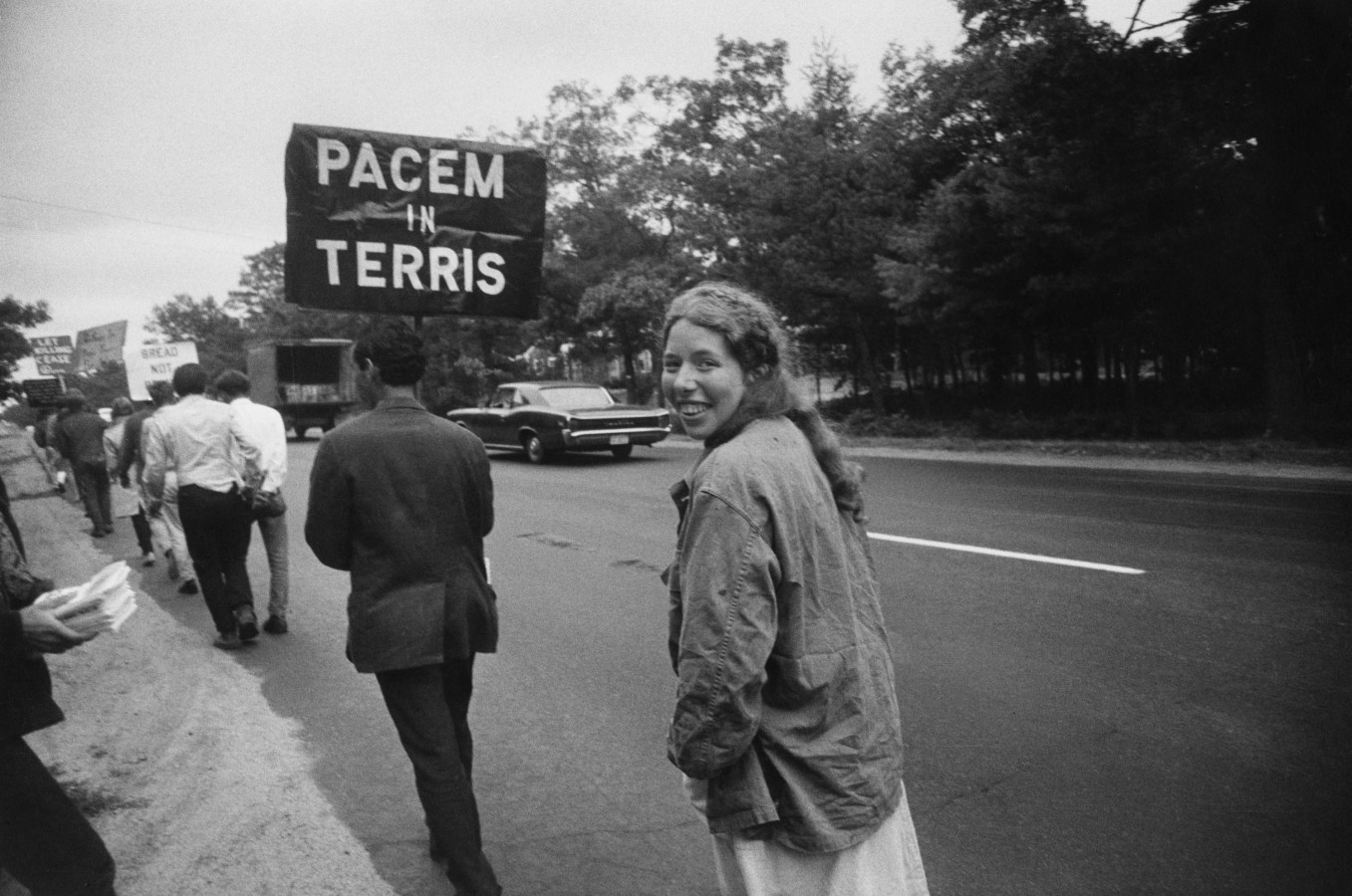 Black-and-white photograph of a woman smiling turning around mid-step following a man with a sign reading PACEM IN TERRIS in a line of people holding signs