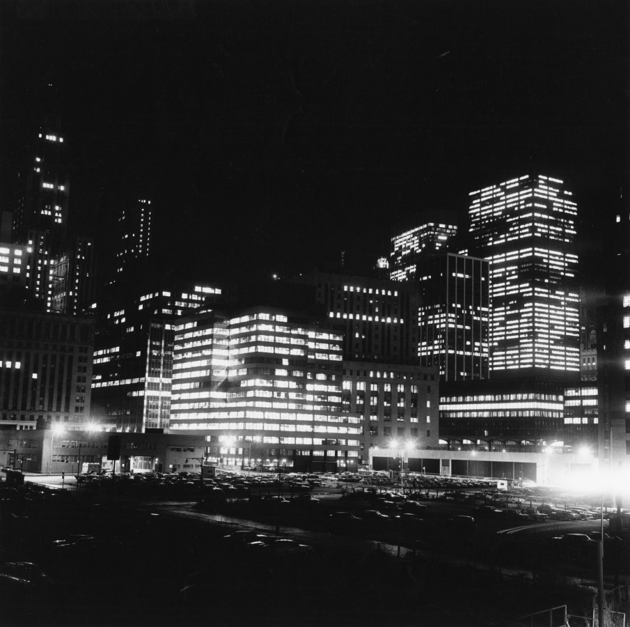 Black-and-white photograph of city buildings lit up from inside standing above a parking lot
