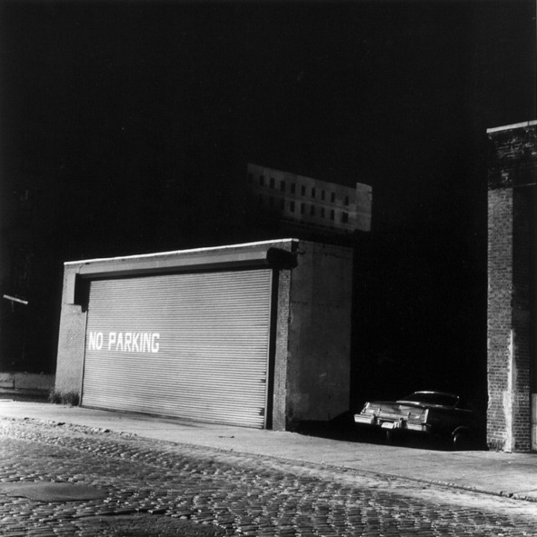 Black-and-white photograph of a shuttered garage door painted with NO PARKING and single car parked in an adjacent driveway on a cobbled street