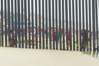 Color photograph of people on a beach behind a tall metal fence running into the ocean