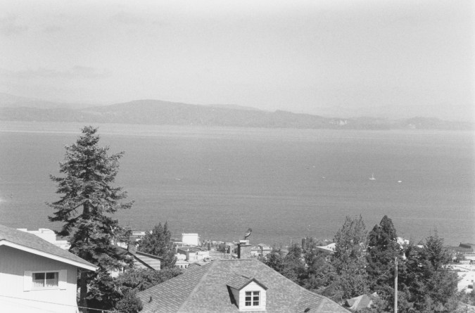 Black-and-white horizontal photograph of the Columbia River, with house rooftops and trees on the close shore and a rising hillside on the far shore.