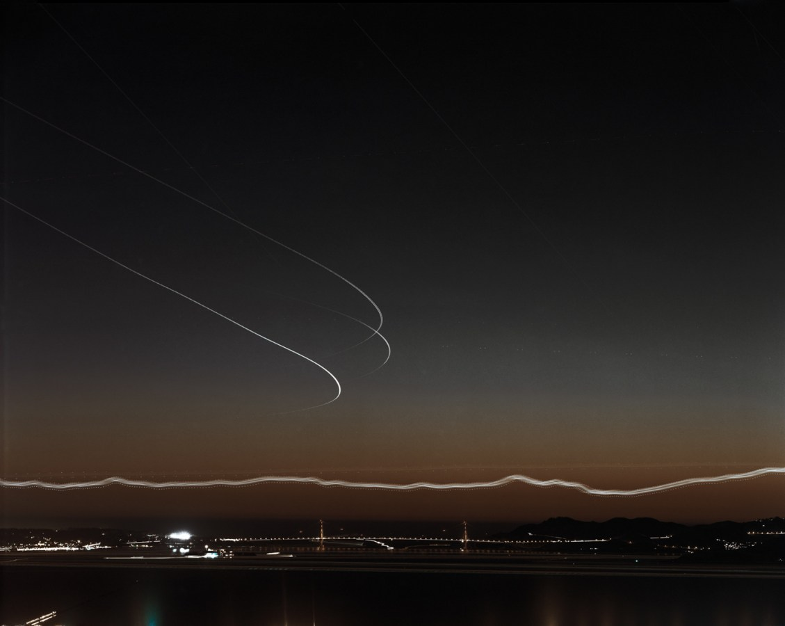 Long-exposure color photograph of the distant Golden Gate Bridge just after sunset under light trails of airplanes