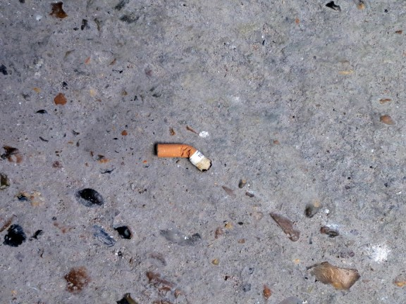 A photograph of a cigarette butt in the sidewalk, on rocky cement