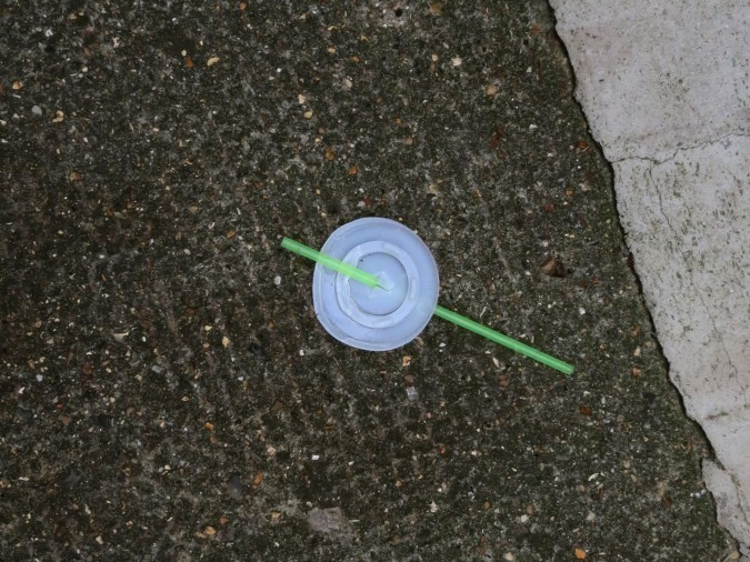 A photograph of a disposable drink lid & green plastic straw in the street