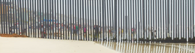 Color photograph of a tall metal fence running into the ocean from the beach, with beach goers visible through the bars