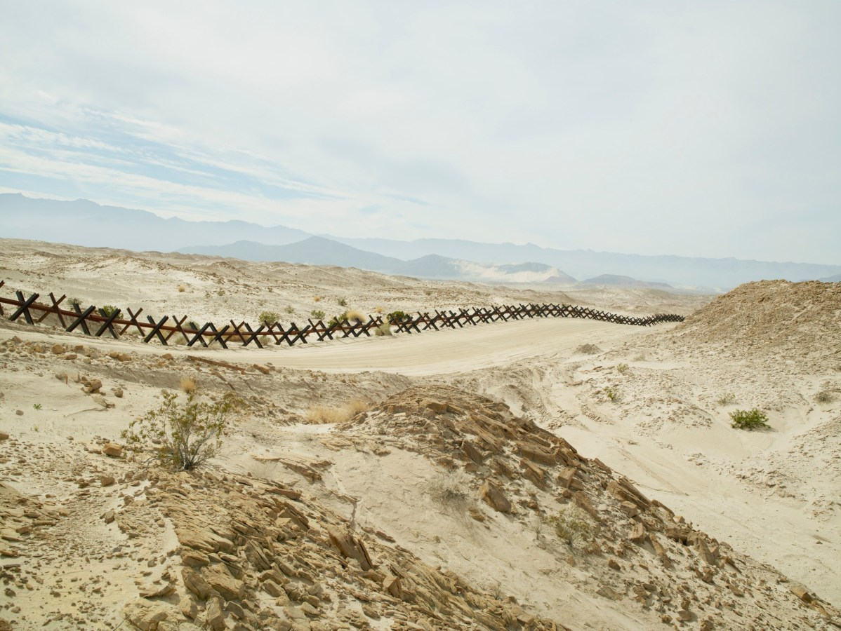 Color photograph of a metal fence made of X-shaped crossbars running through a hilly desert landscape