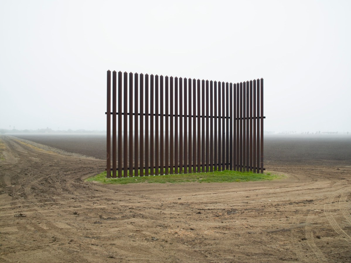 Color photograph of a segment of tall metal fence in the middle of a bare field