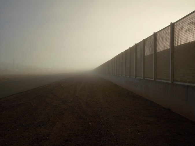 Color photograph of a tall metal and concrete fence receding into the misty horizon on the right