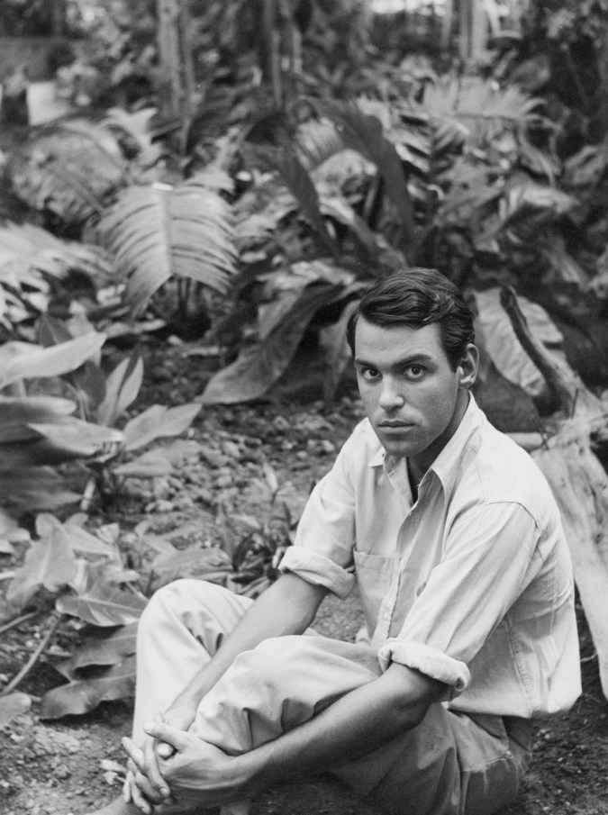 Black-and-white photograph of a white man seated against a backdrop of tropical vegetation.
