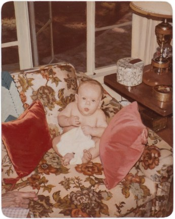 Painting of a baby on a couch surrounded by pillows