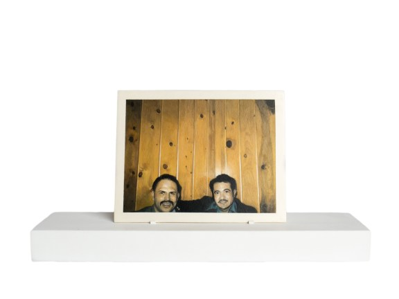 Painting of two men from the neck up in front of a wood paneled wall on a wooden stand