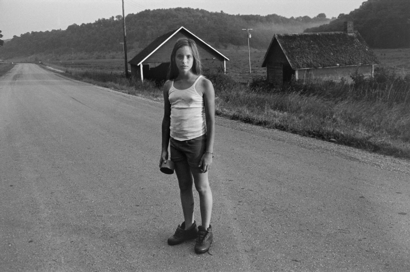 Black-and-white photograph of a girl standing in a dirt road with her head framed by a building in the background