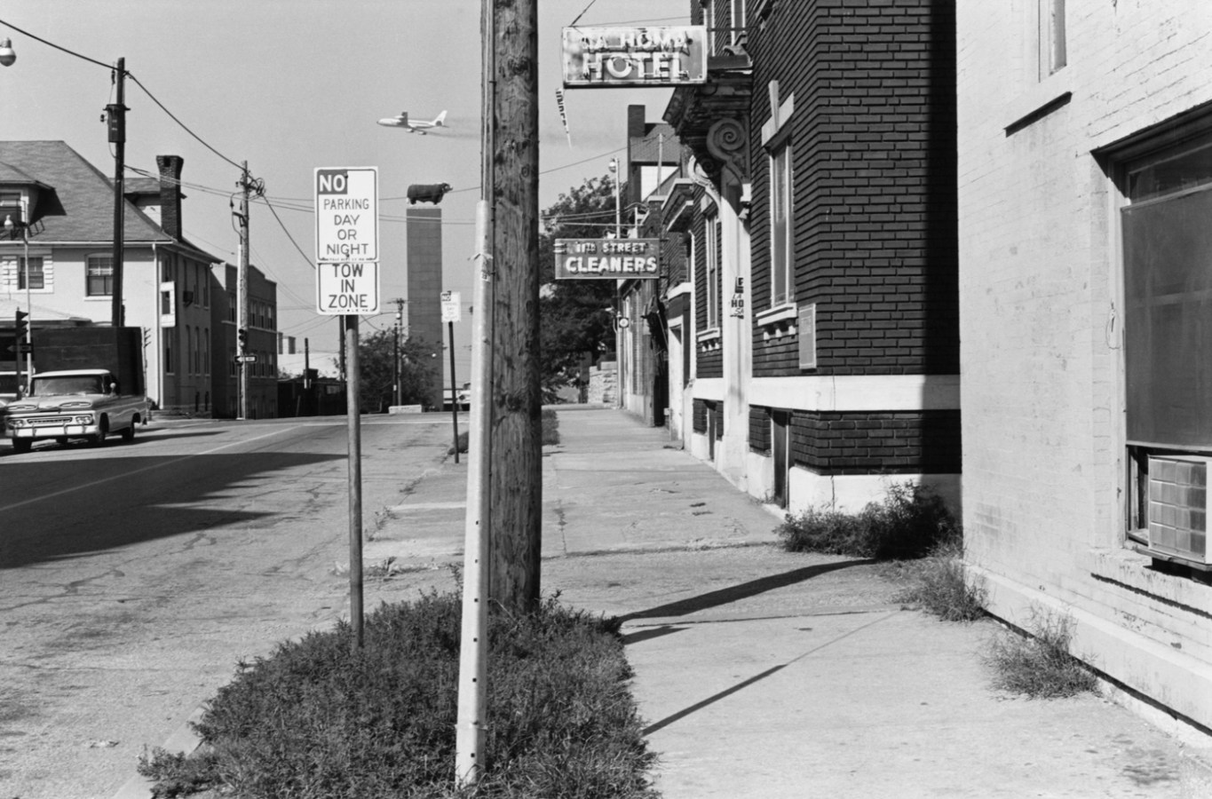 Black-and-white photograph of a city street with a telephone pole in the center
