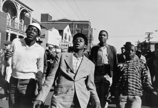 Black and white photograph of four men walking in a crowded street