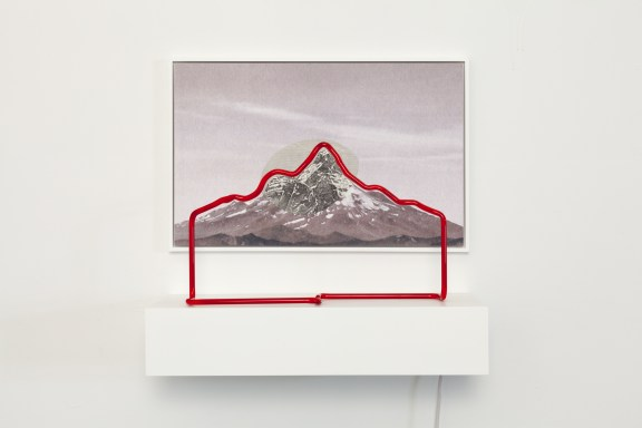 A red neon sculpture (neon turned off) of a mountain silhouette in front of a photograph of the same mountain