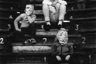 Black-and-white photograph of four figures in Halloween masks seated on a numbered riser.