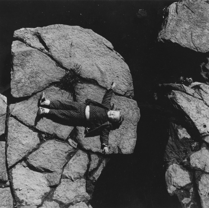 Black-and-white photograph of smiling small girl laying on a boulder.