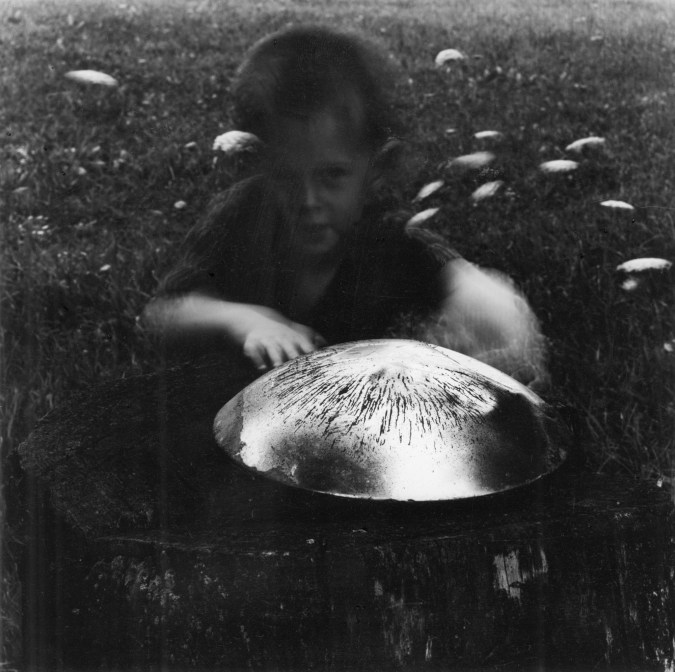 Black-and-white photograph of a young boy crouching behind a hubcap.