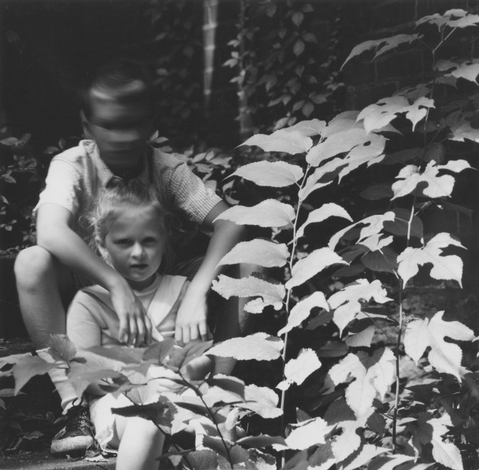 Black-and-white photograph of a small boy and girl seated near a leafy plant