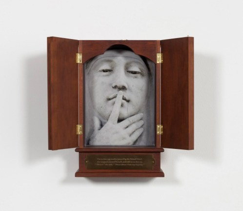 A wooden box with double doors, opened to reveal a photograph of a sculpture of a face with pointer finger to lips