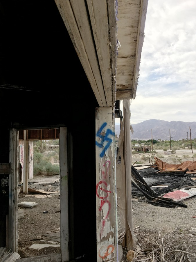 Color photograph of decaying building with various grafitti, including a blue swastika