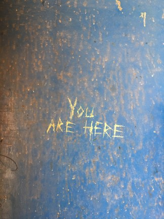 """Color photograph of a surface with peeling blue paint and the scratched inscription """"You are here"""""""