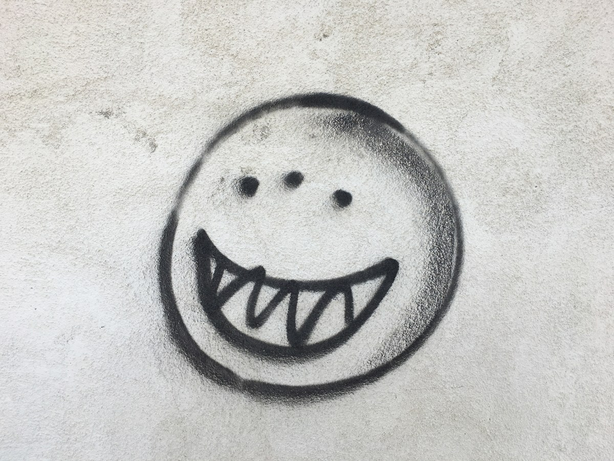 Color photograph of a grey wall with a black spray-painted image of a three-eyed smiley face with jagged teeth.