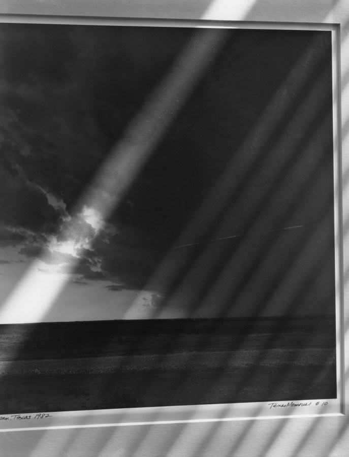 Black-and-white photograph of diagonal stripes of light on a matted photograph of a seascape