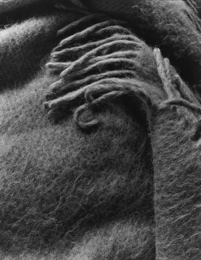 Black-and-white photograph of the corner of a wool shawl with fringed edges