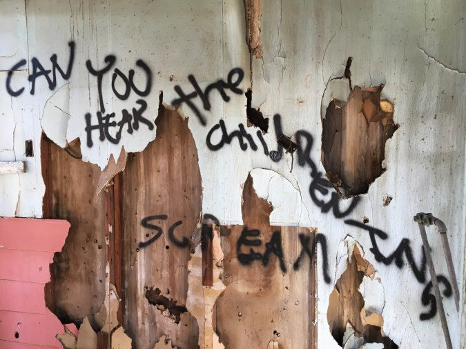 Color photograph of black spray-painted writing on a peeling and partly-demolished white and wooden wall