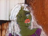 Color photograph of a painting of a woman with green skin on a wooden wall