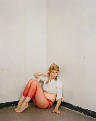 Color photograph of a woman posing in the corner of a room