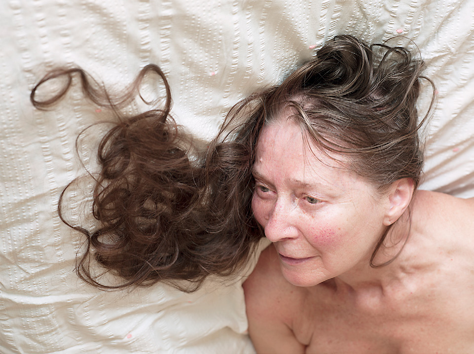 Color photograph of a woman laying down, her hair arranged in curls on the bedsheet.