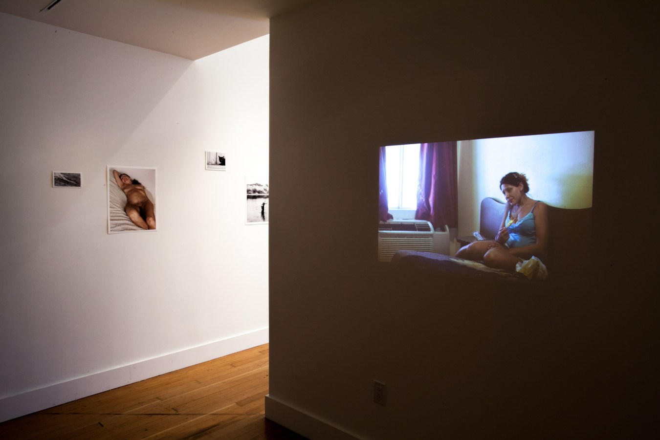 Installation photograph of a gallery space with small unframed prints on the walls and a video projected on one