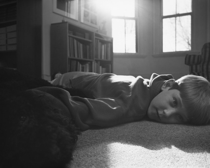 Black-and-white photograph of a boy lying on the floor of a sunny room with his face turned to the viewer