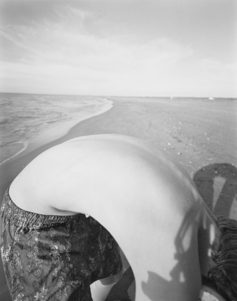 Black-and-white photograph of of a boy's bent-over back against the backdrop of a seashore
