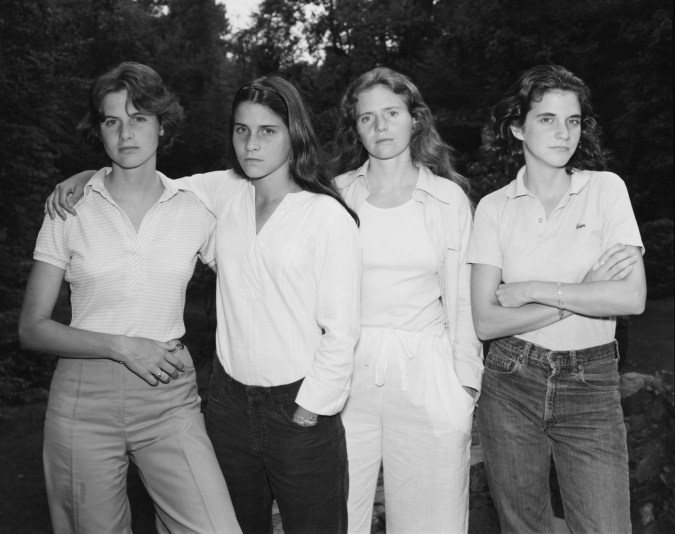 Black and white photograph of four women standing shoulder to shoulder in a garden