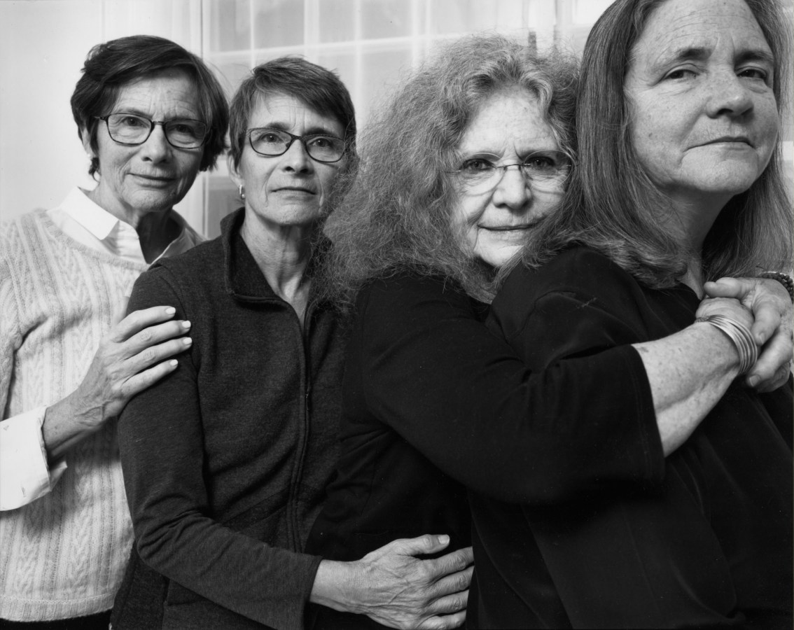 Black-and-white photographic portrait of four older women with their arms around each other standing in front of a curtained window