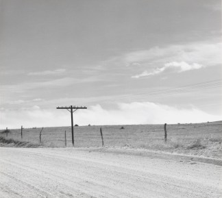 A black and white photograph of a road, with sky in the first half of the photograph. A telephone pole is in the center left