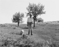 A black and white photograph of a woman and a small white dog trees in the background.
