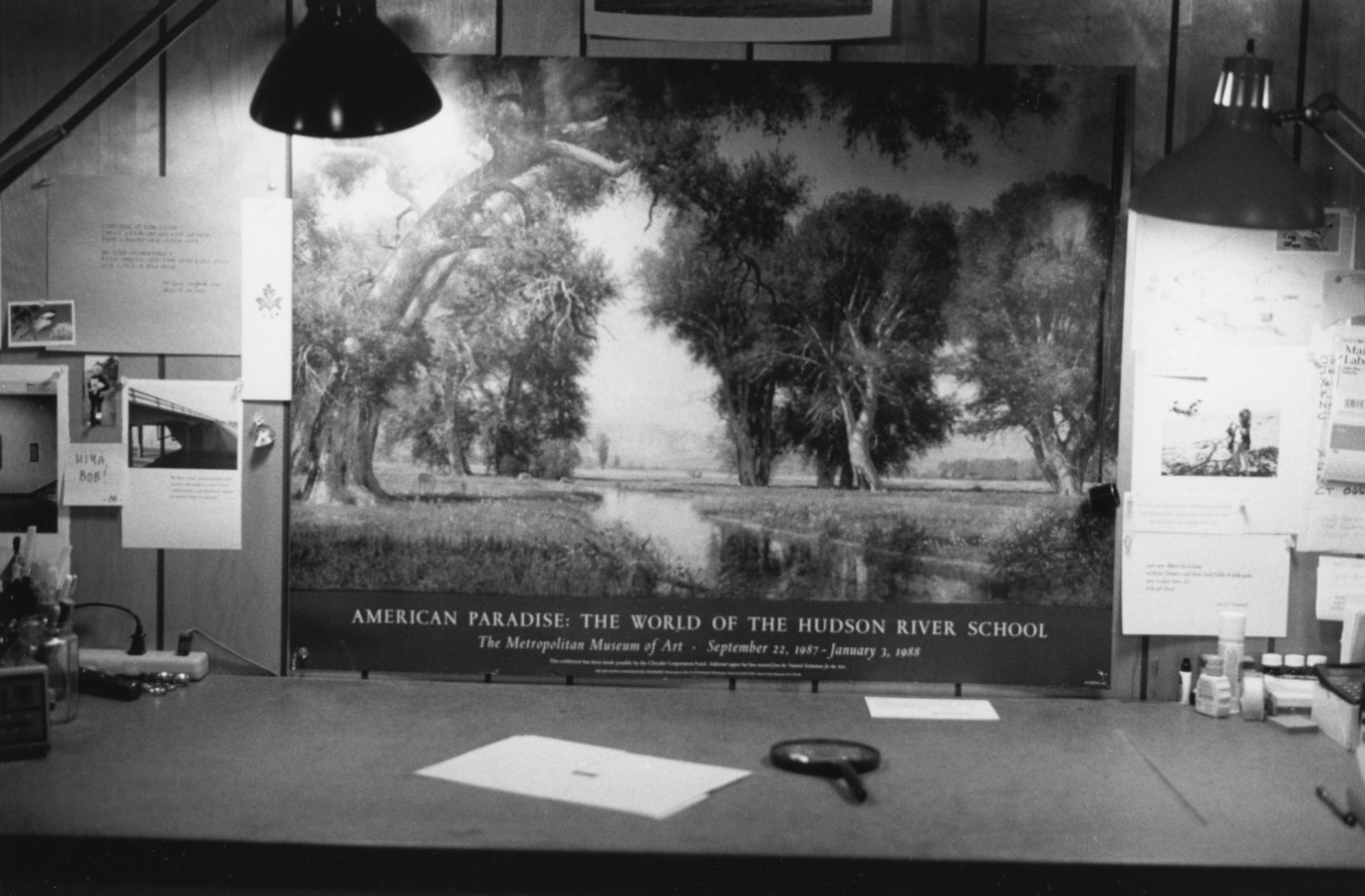 """Black-and-white horizontal photograph of a desk with papers and a magnifying glass on the surface and a poster for the """"Hudson River School"""" in the background"""