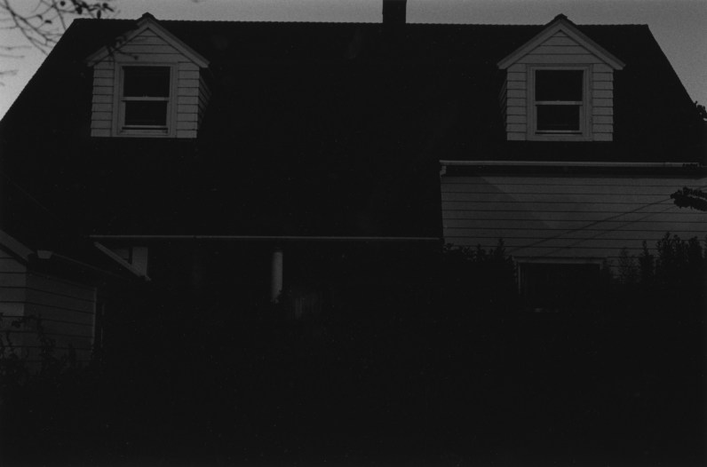 black-and-white vertical photo of a dimly lit house with two dormers