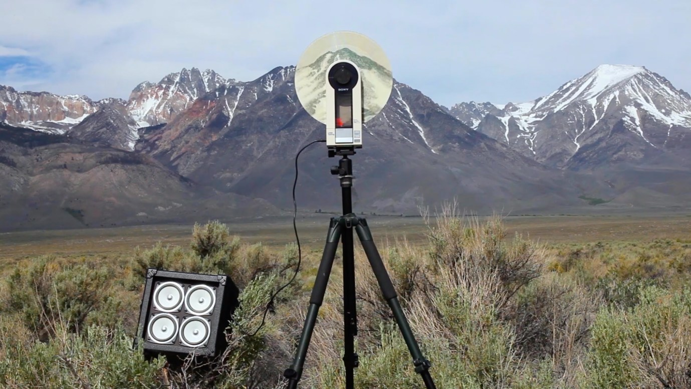 Color photograph of a camera mounted on a tripod against the background of a valley and mountain range