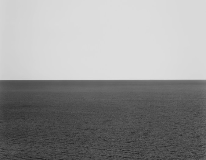 Black-and-white photograph of a calm seascape across the lower half with a light gray sky above