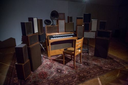 An organ surrounded by speakers of various sizes and vintages, and an empty chair on an ornate carpet