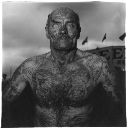 Black-and-white photograph of a shirtless tattooed man with flags and storm clouds in the background
