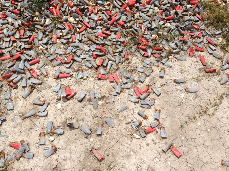Color photograph of scattered red ammunition casings lying on a bare cracked ground
