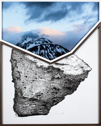 A framed photograph of a mountain top and clouds resting on a framed drawing of a rock in the same shape.